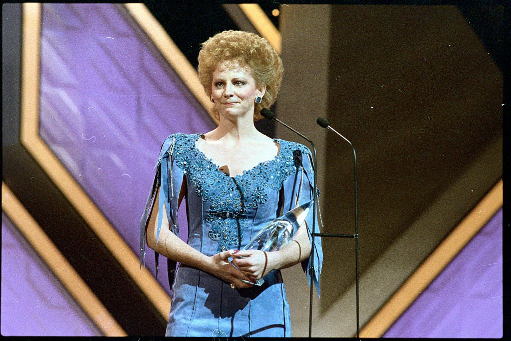 "Image Credits: Getty Images /  Bettmann | Reba receiving the award for ""Entertainer of the Year"""