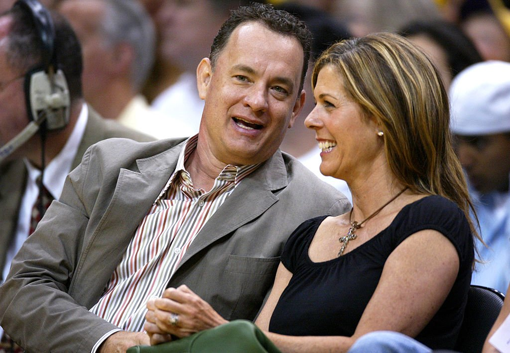 Image Credits: Getty Images / Vince Bucci | Actor Tom Hanks and wife Rita Wilson attend Game 6 of the NBA Western Conference Semifinals between the San Antonio Spurs and the Los Angeles Lakers on May 15, 2004 in Los Angeles, California.