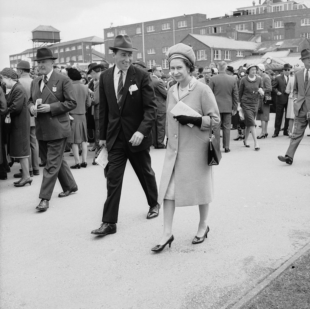 Image Credits: Getty Images / Roger Jackson / Central Press | Queen Elizabeth II and Lord Porchester at Newbury Races. Lord Porchester took over from Michael Oswald as the Queen's racing manager in 1970.