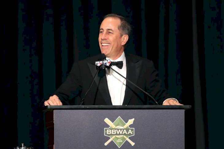 Image Credit: Getty Images / Jerry Seinfeld speaks to the crowd during the 2020 Baseball Writers' Association of America awards.