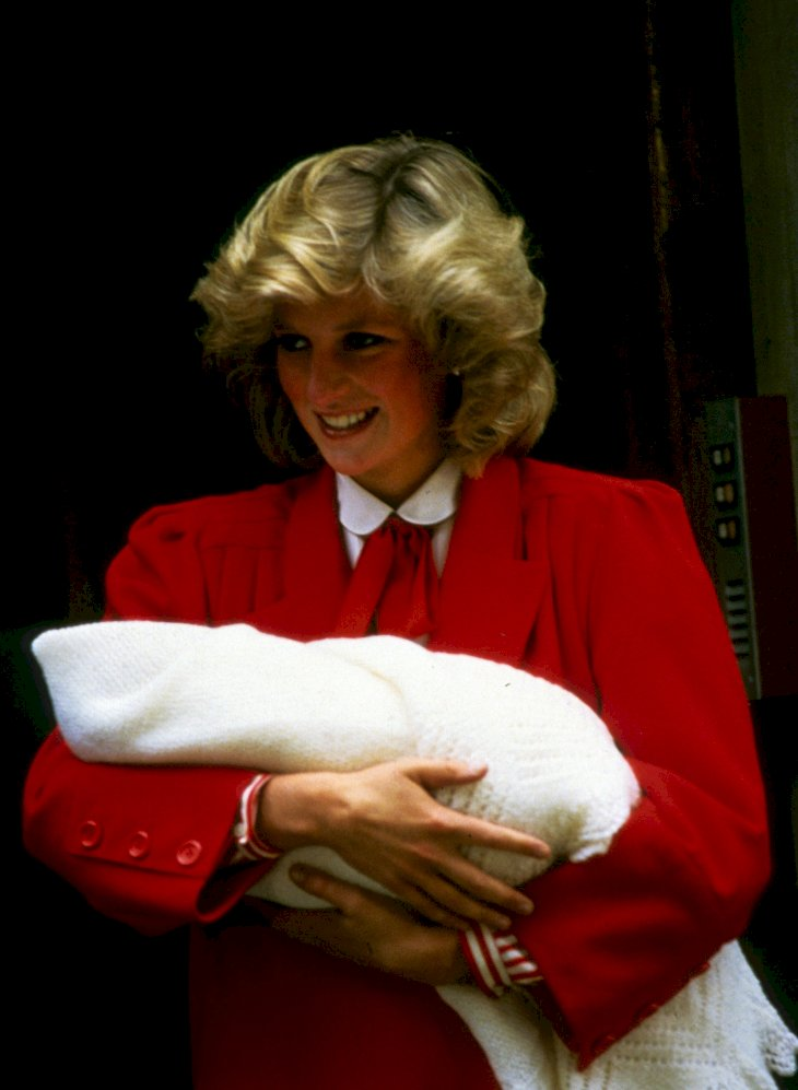 Image Credit: Getty Images / Princess Diana showing a newborn Prince Harry to the world.