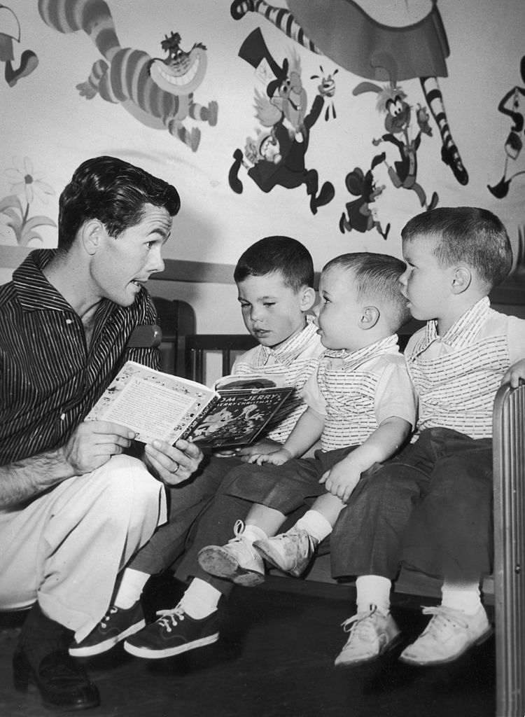 Image Credits: Getty Images / Hulton Archive | American television host Johnny Carson kneels while he reads a children's book to his sons (L-R): Kit, Cory and Ricky, in their nursery. There are cartoon characters on the wall behind them.