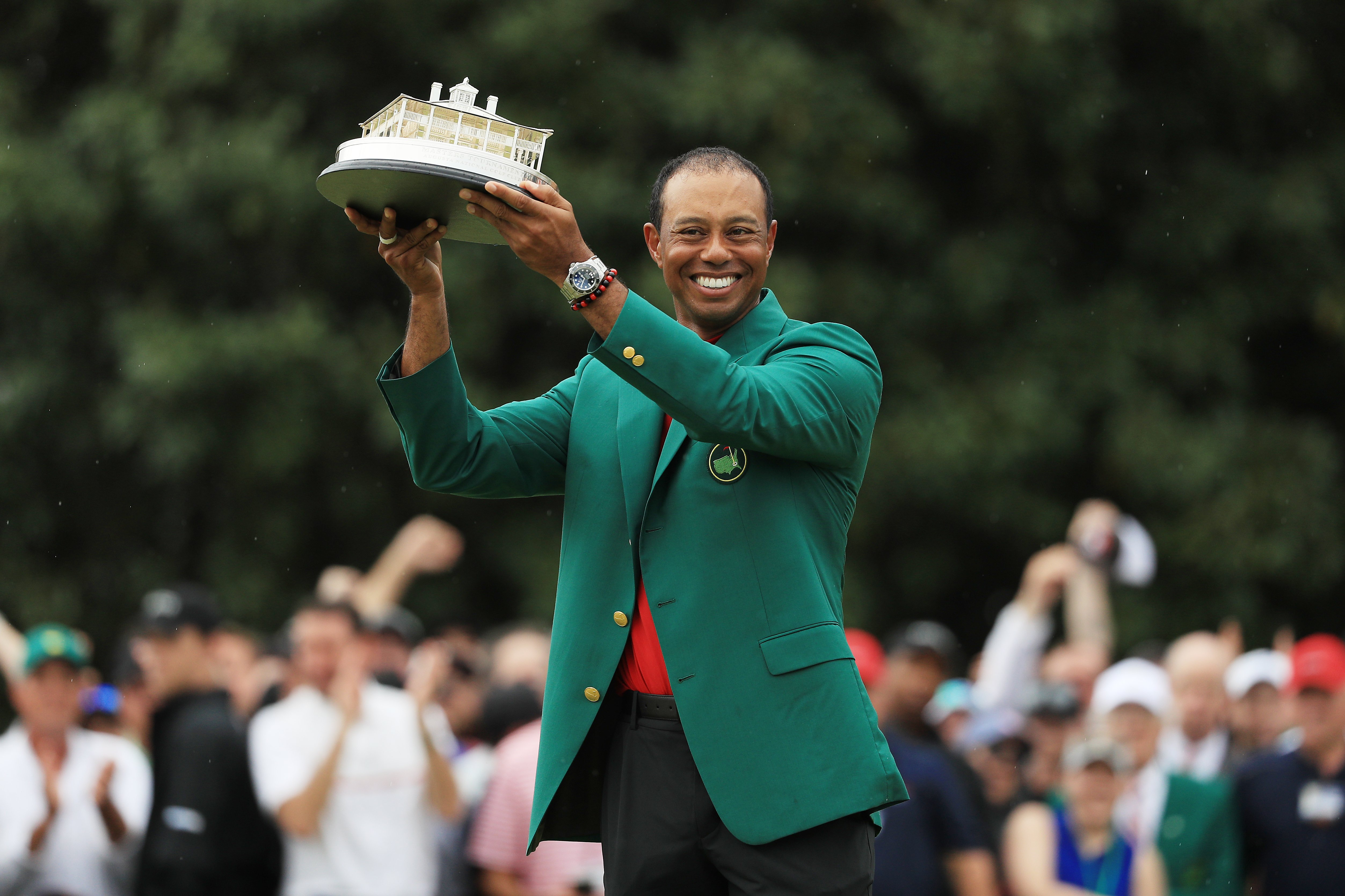 Image Credits: Getty Images / Mike Ehrmann | Tiger Woods of the United States celebrates with the Masters Trophy during the Green Jacket Ceremony after winning the Masters at Augusta National Golf Club on April 14, 2019 in Augusta, Georgia.