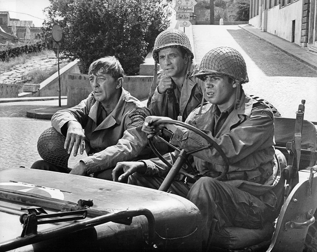 Image Credits: Getty Images / Columbia Pictures | Robert Mitchum, Peter Falk, and Reni Santoni seem perplexed as they enter a deserted Rome in a scene from the film 'Anzio', 1968.