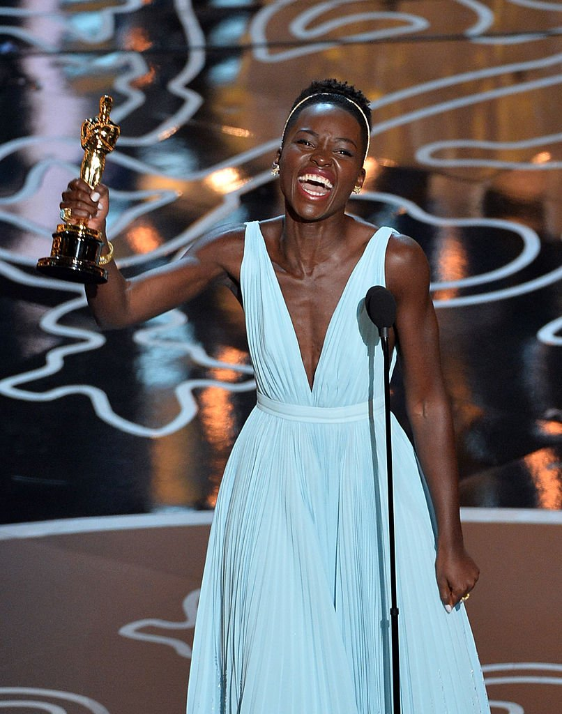 Image Credits: Getty Images / Kevin Winter | Actress Lupita Nyong'o accepts the Best Performance by an Actress in a Supporting Role award for '12 Years a Slave'