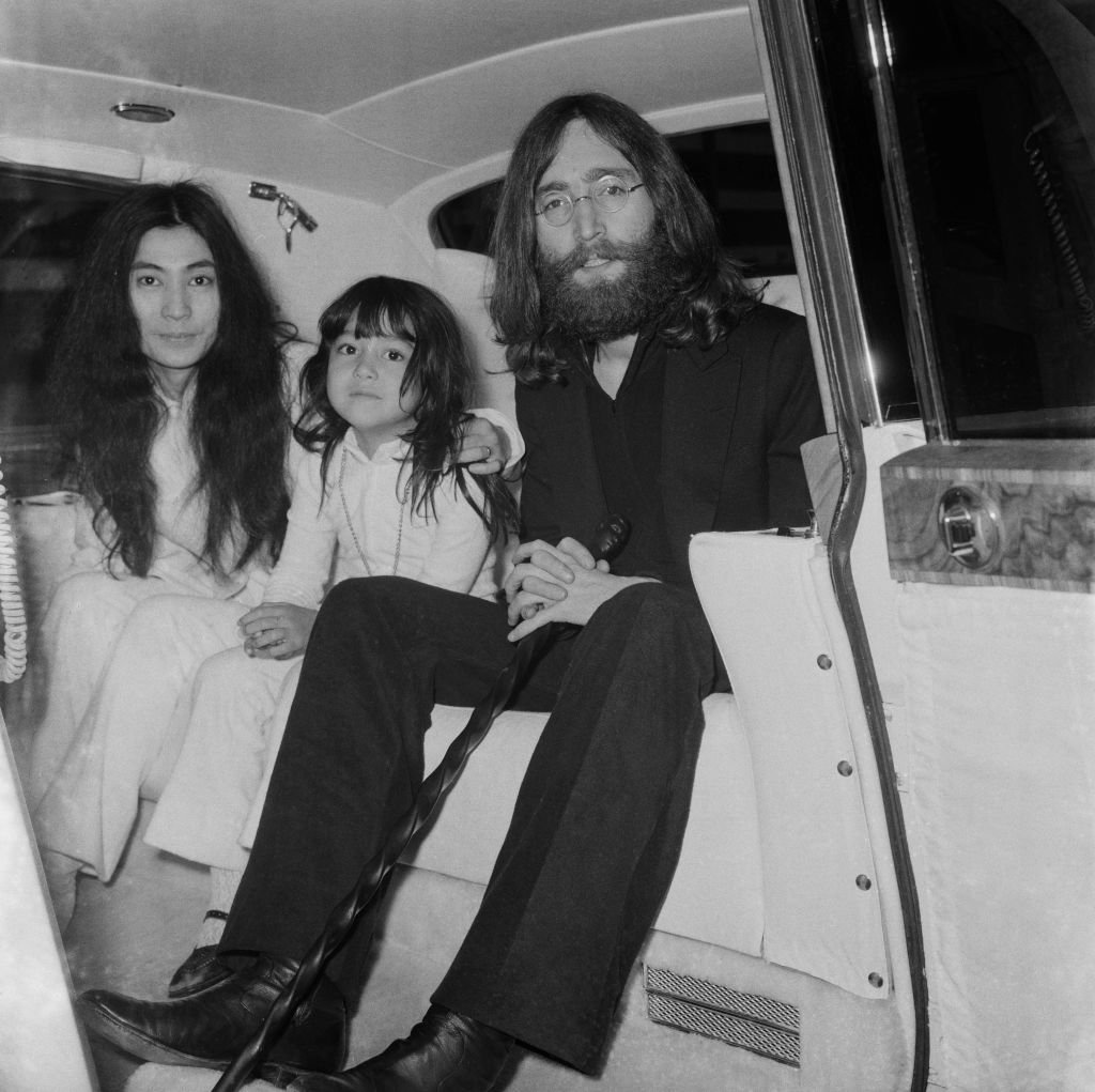 Image Credits: Getty Images / George Stroud / Daily Express / Hulton Archive | Japanese multimedia artist, singer, songwriter, and peace activist Yoko Ono with her daughter Kyoko Chan Cox and her husband English singer, songwriter, and peace activist John Lennon (1940 -1980) of The Beatles, at Heathrow Airport, London, UK, 7th June 1969.