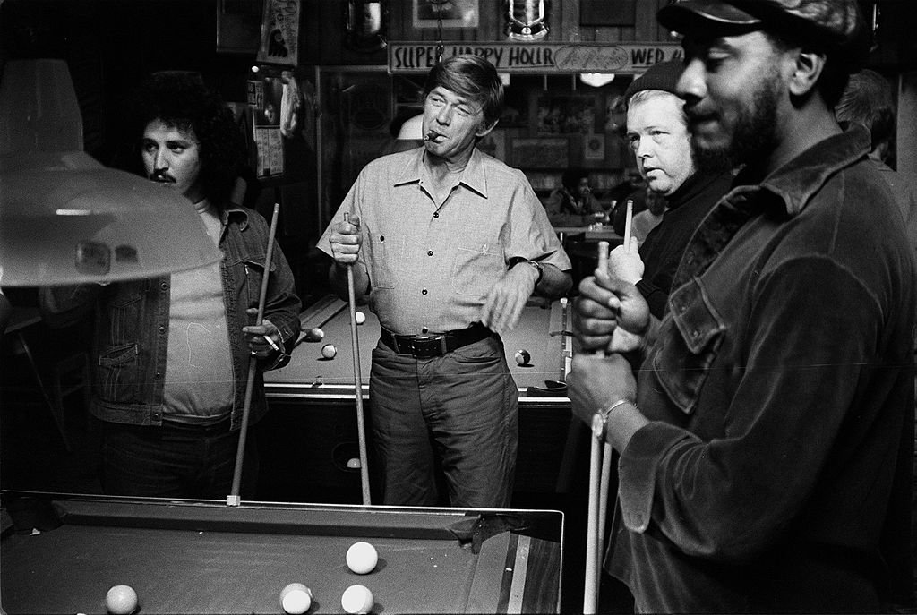 Image Credits: Getty Images / CBS | American actor Ralph Waite smokes a cigar and enjoys a game of pool with his buddies in a scene from the made-for-television movie 'The Secret Life of John Chapman,' 1976. Waite stars as college president John Chapman who goes on sabbatical and takes a series of blue-collar jobs in order to see what life was like outside of the halls of academia in this GE Theater Special.