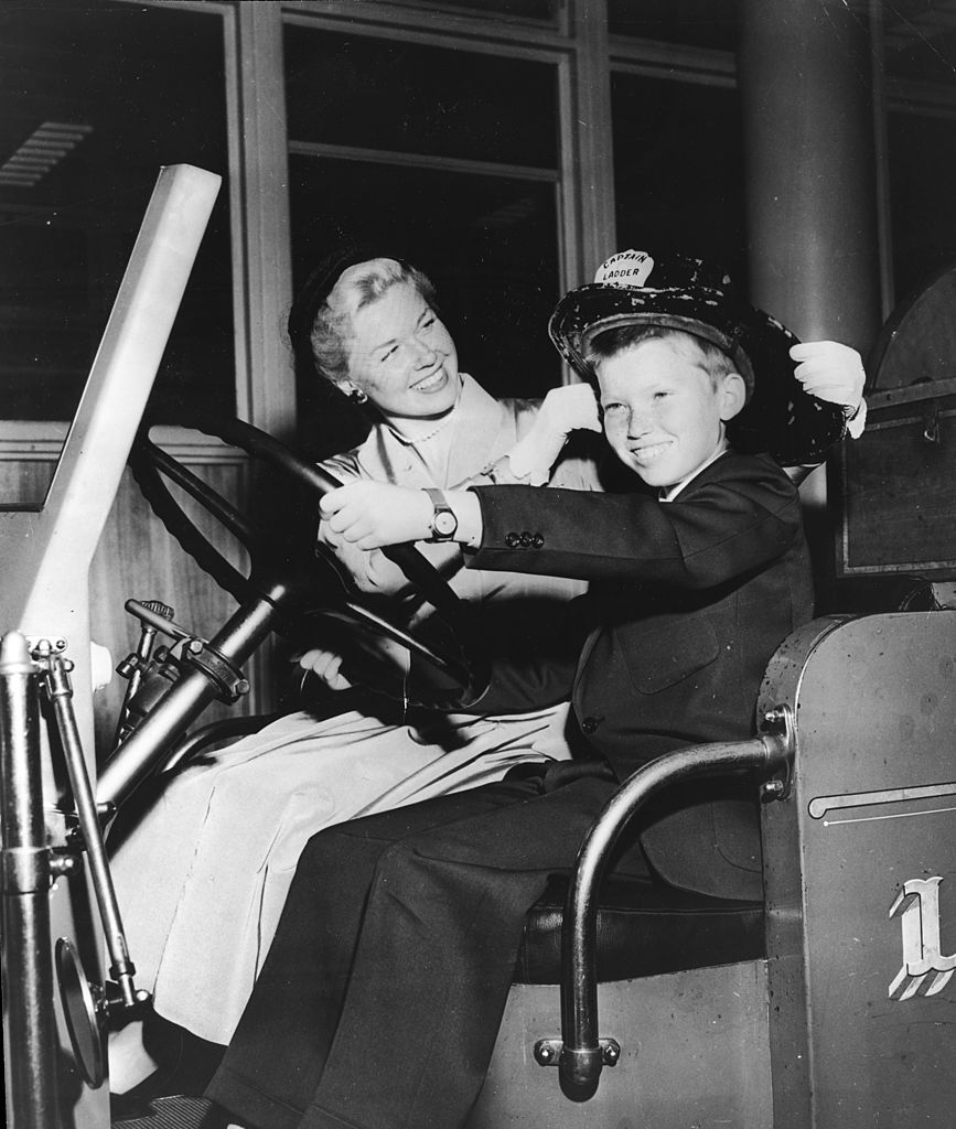 Image Credits: Getty Images / Hulton Archive | American actor and singer Doris Day smiling as she sits next to her son, Terry, in a fire truck, Cincinnati, Ohio. Day was visiting relatives in her hometown of Cincinnati while promoting the film 'By the Light of the Silvery Moon.'