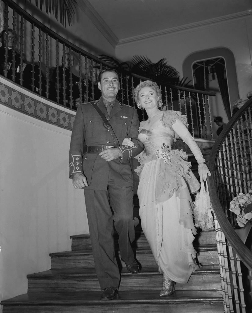 Image Source: Getty Images/Fred MorleyEnglish actress Anna Neagle (1904 - 1986) and actor Errol Flynn (1909 - 1959) enter a reproduction of Romano's Restaurant on the Strand at the ABC studios in Elstree, UK, during the filming of 'Lilacs in the Spring', 3rd June 1954