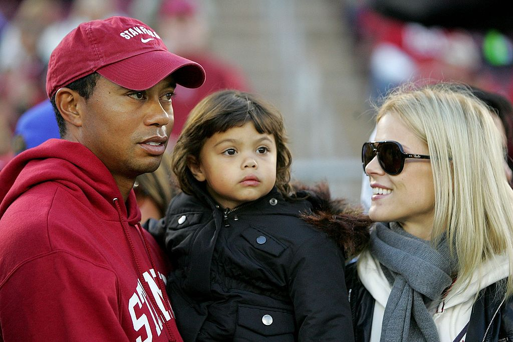 Image Credits: Getty Images / Ezra Shaw | Honorary Standford Cardinal captain Tiger Woods holds his daugher, Sam, and speaks to his wife, Elin Nordegren, on the sidelines before the Cardinal game against the California Bears at Stanford Stadium on November 21, 2009 in Palo Alto, California.