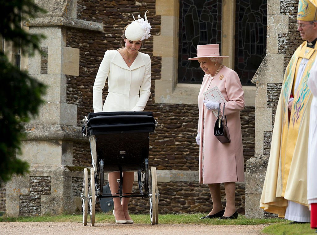 Image Credit: Getty Images / Queen Elizabeth II speaks to Catherine, Duchess of Cambridge, as she pushes baby Princess Charlotte of Cambridge on July 5, 2015 in King's Lynn, England.
