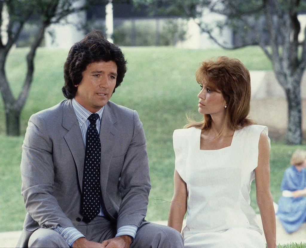 Image Credit: Getty Images / In a scene from the American television series 'Dallas,' American actors Patrick Duffy (as Bobby Ewing) and Victoria Principal (as Pamela Barnes Ewing) sit outside.