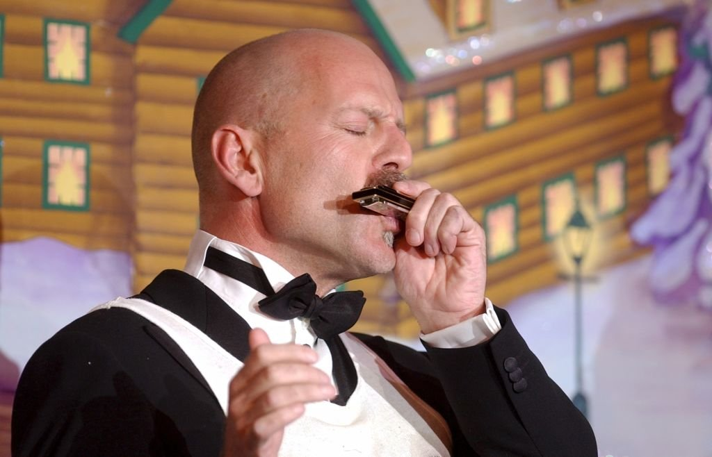 Image Credit: Getty Images / Harvard's Hasty Pudding Club's Man of the Year Bruce Willis plays harmonica before receiving the traditional pudding pot on stage at the Club.