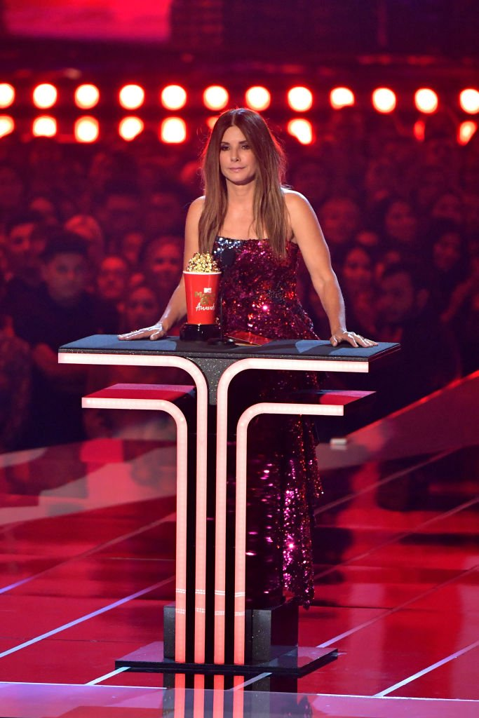 Image Credits: Getty Images / Amy Sussman | Sandra Bullock accepts award onstage during the 2019 MTV Movie and TV Awards at Barker Hangar on June 15, 2019 in Santa Monica, California.
