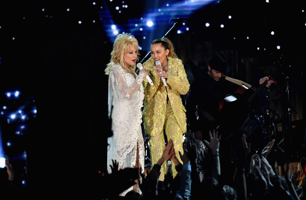 Image Credits: Getty Images / Jeff Kravitz / FilmMagic | Dolly Parton (L) and Miley Cyrus perform onstage during the 61st Annual GRAMMY Awards at Staples Center on February 10, 2019 in Los Angeles, California.
