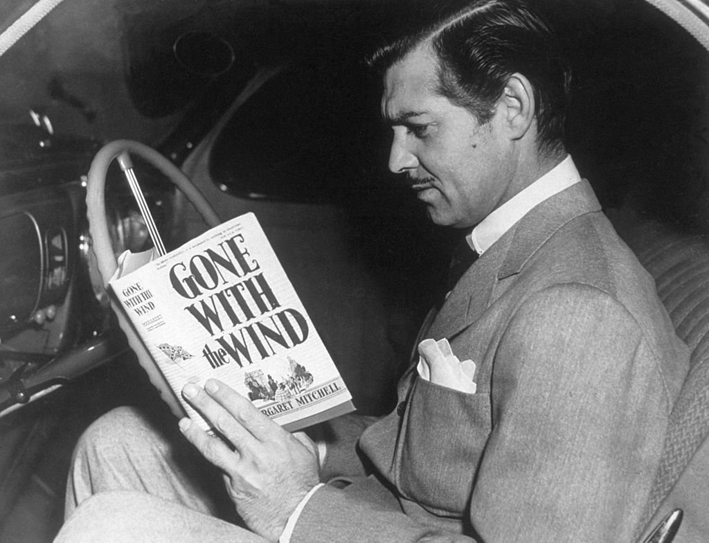 Image Credit: Getty Images / American film star Clark Gable reading the novel 'Gone With the Wind' by Margaret Mitchell
