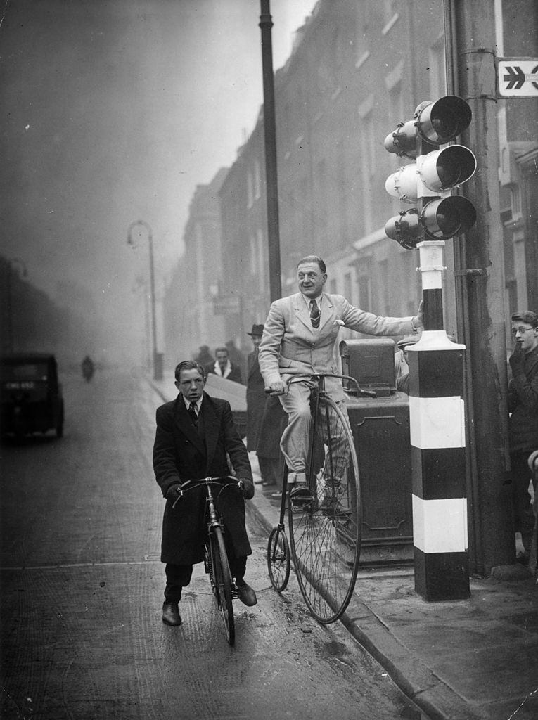 16th February 1938: Mr C A Denny, a former Olympic cyclist stops at traffic lights whilst riding a 52-year-old penny farthing to the London offices of the National Cyclists' Union. Image Source: Getty Images