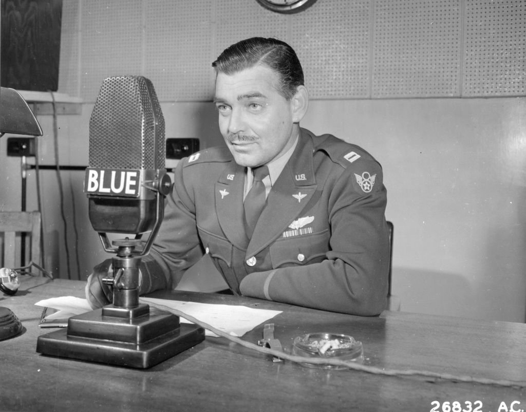 Image Credit: Getty Images / Capt Clark Gable speaks into a microphone in England, 1943.