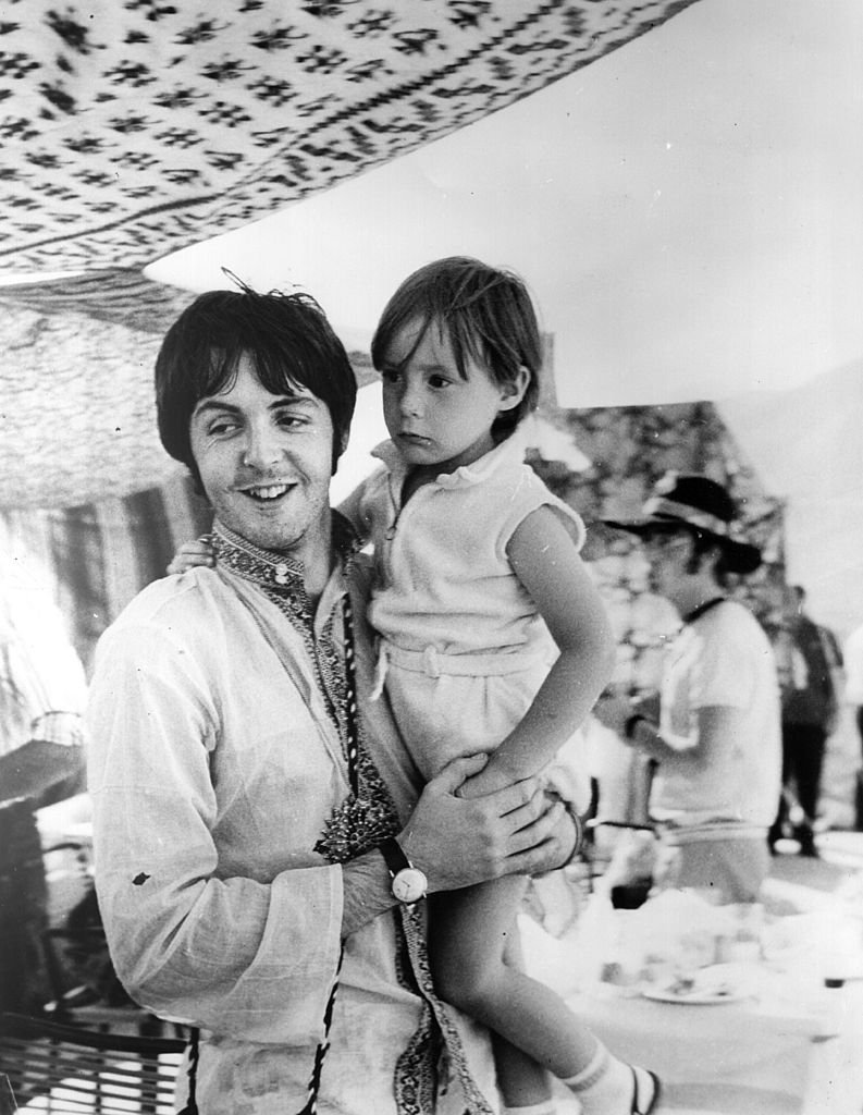 Image Credits: Getty Images / Central Press | Beatles singer and bass player Paul McCartney holds four year old Julian, son of his colleague John Lennon (visible in the background) during a holiday near Athens in Greece.