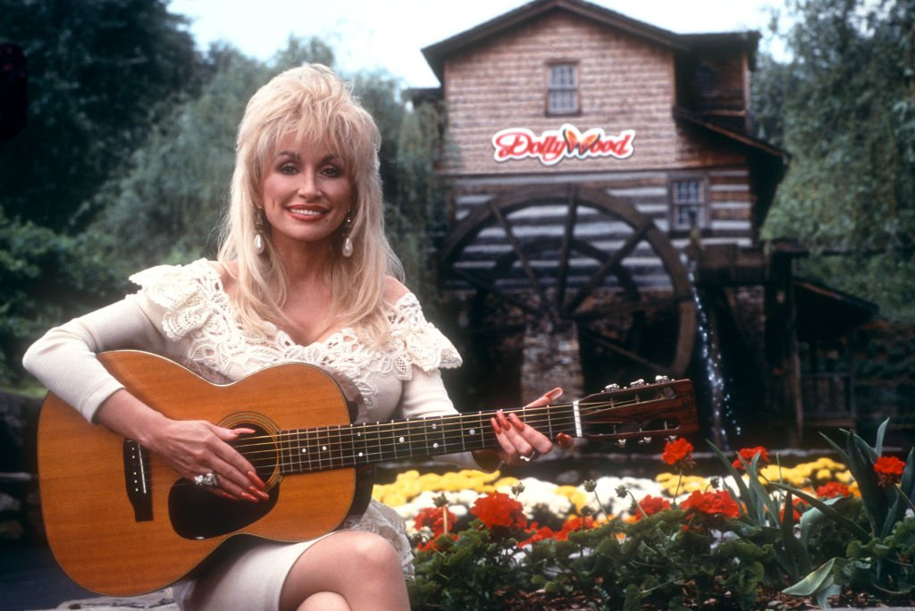 Image Credits: Getty Images / Ron Davis | American singer and songwriter Dolly Parton poses for a portrait with her guitar at Dollywood circa 1993 in Pigeon Forge, Tennessee.